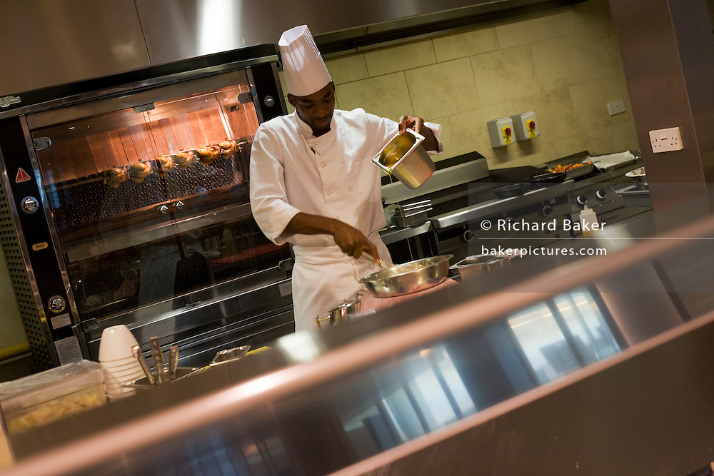 A chef pours liquids in the kitchens at the Vivre restaurant in Sofitel.