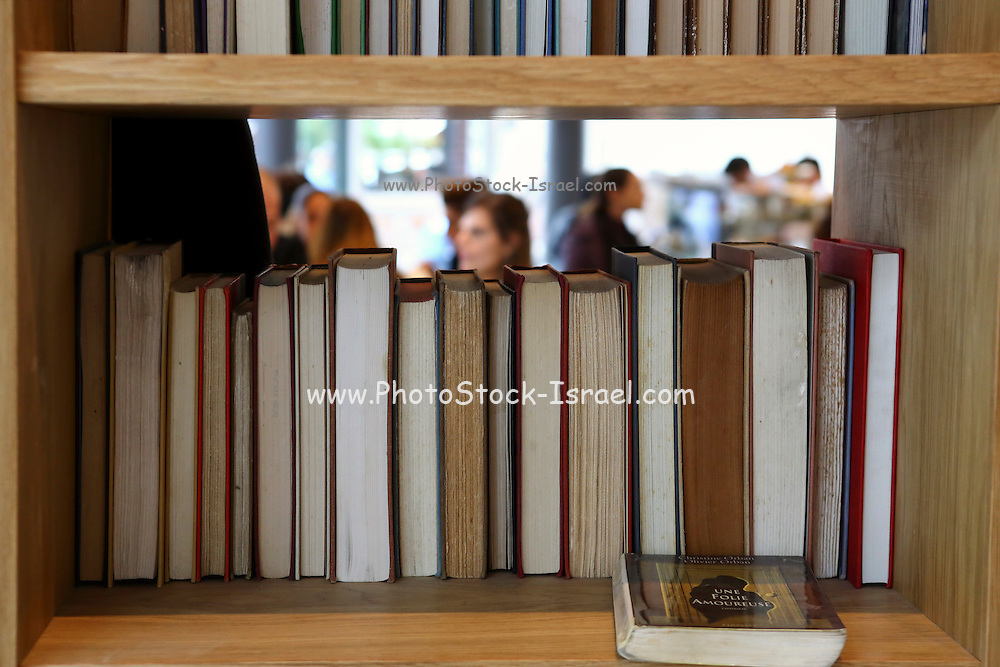books in a bookshelf with out of focus people in the background