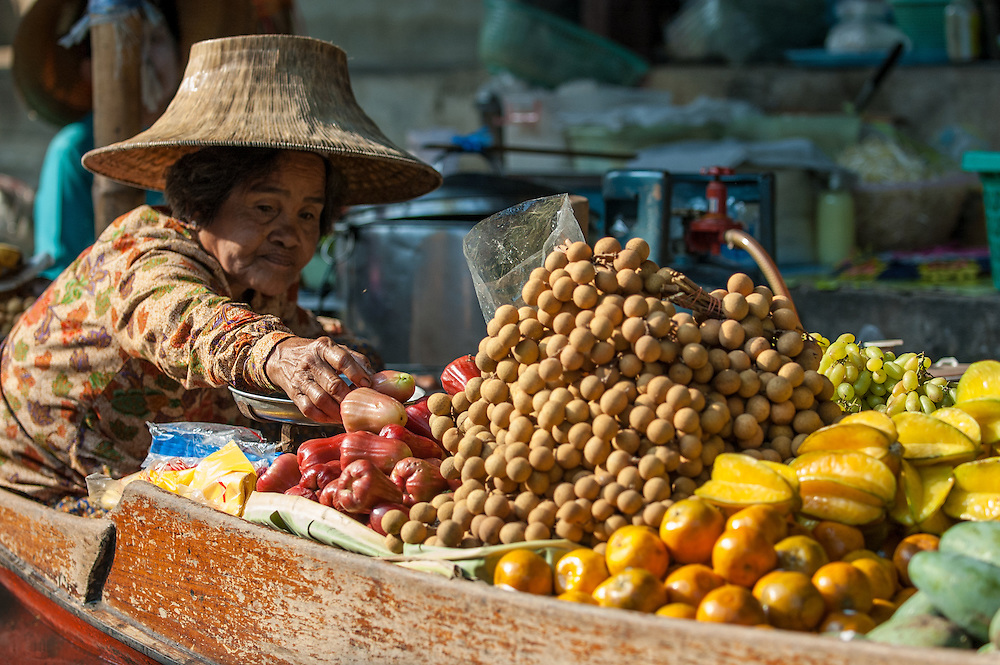 Old woman selling fruit from her canoe at the Floating Market in Damnoensaduak, Thailand. She is a villager selling her wares from a canoe or row boat in the canals west of Bangkok.