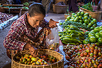 BAGAN, MYANMAR - CIRCA DECEMBER 2013: Burmese woman buying vegetables in the Nyaung U market close to Bagan in Myanmar