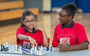 Arial Baker, left, and Kailee Bradford plot their next move against chess grandmaster Susan Polgar during their game at Ryan Middle School, September 15, 2014.