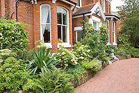 front garden of a large detached house with red gravel driveway and holly bushes