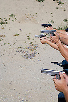 Peoples aiming guns at firing range, close up of hands