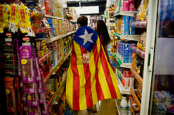 October 26, 2017 - Barcelona, Catalonia, Spain - A woman  wrapped with a estelada or pro-independence flag is seen in a supermarket in Barcelona. In Barcelona thousands of students marched demanding Catalan regional president  Carles Puigdemont to declare independence. (Credit Image: © Jordi Boixareu via ZUMA Wire)