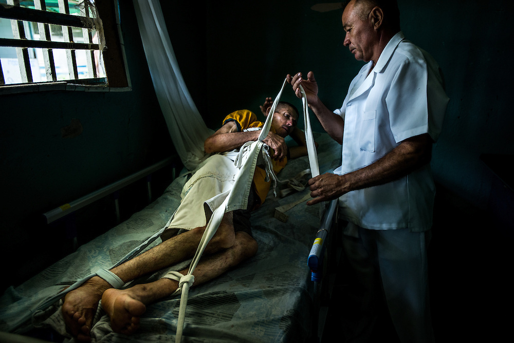 BARQUISIMETO, VENEZUELA - JULY 29, 2016: A nurse restrains Raúl Martínez, a paranoid schizophrenic who also suffers from depression during an episode when he lost control and was at risk of hurting himself. He did not have all of the medicines that he required to keep him stable, because of the shortages.  The economic crisis that has left Venezuela with little hard currency has also severely affected its public health system, crippling hospitals like El Pampero Psychiatric Hospital by leaving it without the resources it needs to take care of patients living there, the majority of whom have been abandoned by their families and rely completely on the state to meet their basic needs. The hospital has not employed a psychiatrist for over two years. Drugs used to combat bipolar disorder, epilepsy, schizoaffective disorder and chronic anxiety are now in short supply, as are numerous sedatives and tranquilizers needed to care for patients. Members of the nursing staff debate daily which patients are the most unstable, to decide which patients will receive pills and which will go without. When a patient loses control, often the only thing they can do is restrain them, or lock them in an isolation cell to prevent them from hurting themselves, other patients and members of the staff.  PHOTO: Meridith Kohut