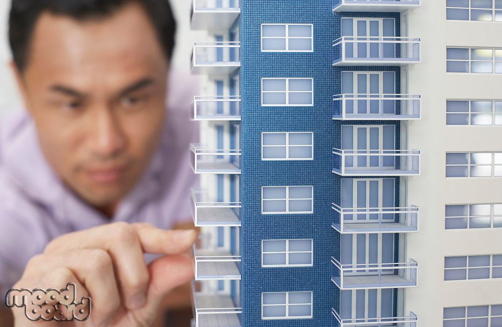 Mid adult man inspecting architectural model close-up
