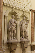 The statues of Sir Eyre-Coote, K.B. by Thomas Banks (1788) and   <br /> Marquis Cornwallis, K.G. by John Bacon, Senior (1791) in the Gurkha Stair in the former India Office, which was part of the Foreign and Colonial Office (now the Foreign and Commonwealth Office), Whitehall, London. on 17th September 2017, in Whitehall, London, England. The main Foreign Office building is in King Charles Street, and was built by George Gilbert Scott in partnership with Matthew Digby Wyatt and completed in 1868 as part of the new block of government offices which included the India Office and later (1875) the Colonial and Home Offices. George Gilbert Scott was responsible for the overall classical design of these offices but he had an amicable partnership with Wyatt, the India Office's Surveyor, who designed and built the interior of the India Office.