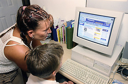 Single mother teaching young son to use computer,