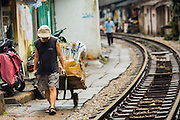07 APRIL 2012 - HANOI, VIETNAM: A man pulls a cart of recyclable paper and cardboard along the train tracks in Hanoi, the capital of Vietnam. Hanoi is one of the oldest cities in Southeast Asia. It was established in 1010 A.D.   PHOTO BY JACK KURTZ