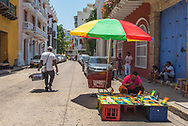 Cartagena, Colombia -- April 21, 2018. An artist works on a painting under an umbrella; a delivery man walks on a side street in Cartagena, Columbia.  Editorial use only.