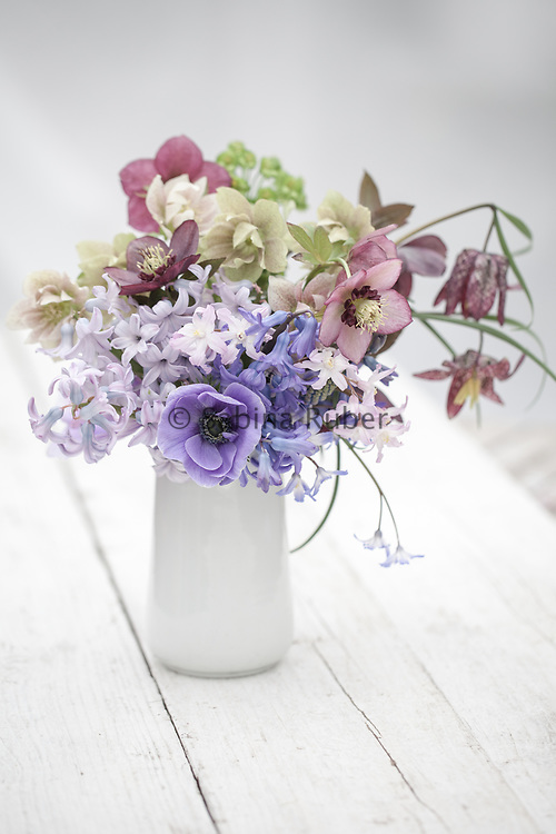 Spring flower arrangement with blue Anemone coronaria, hellebores, hyacinths and snake's head fritillarys