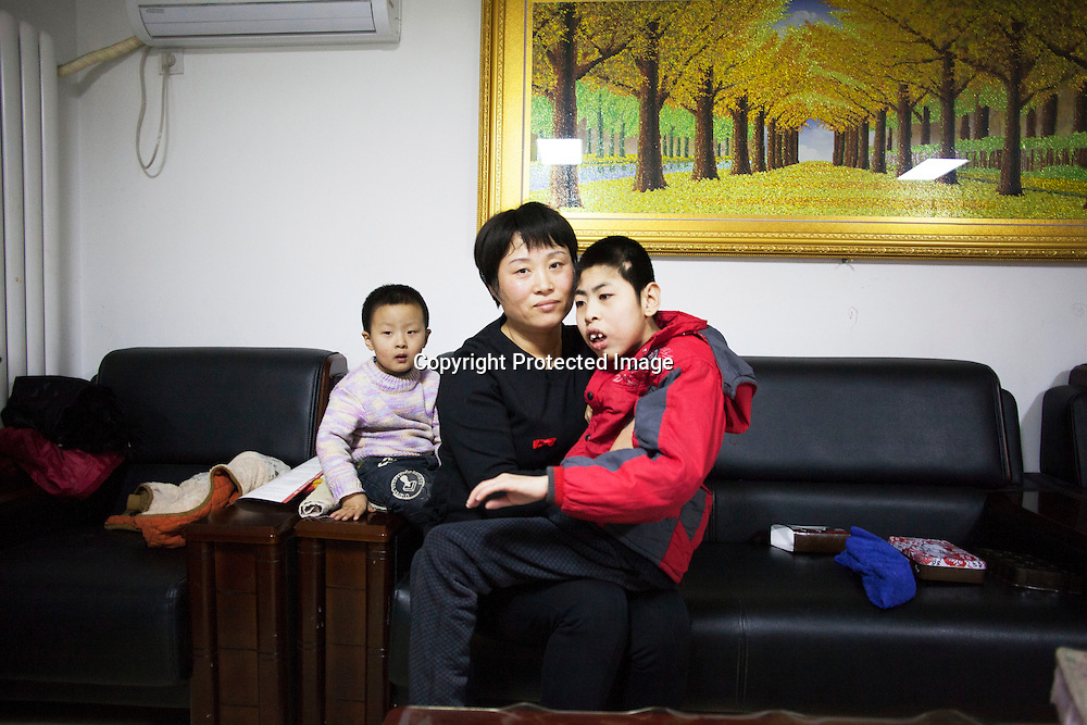 Beijing, March 11 : Tian Peng, 15, is taken care of by his mother Cui Xinying while his little brother Tian Ye, 3, sits next to them on the sofa.<br />