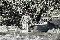 Walking a drift boat skiff down a riffle on a secluded creek in the Ozarks
