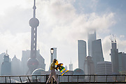 A man flies a kite early morning on the Bund against the skyline of modern Shanghai, China