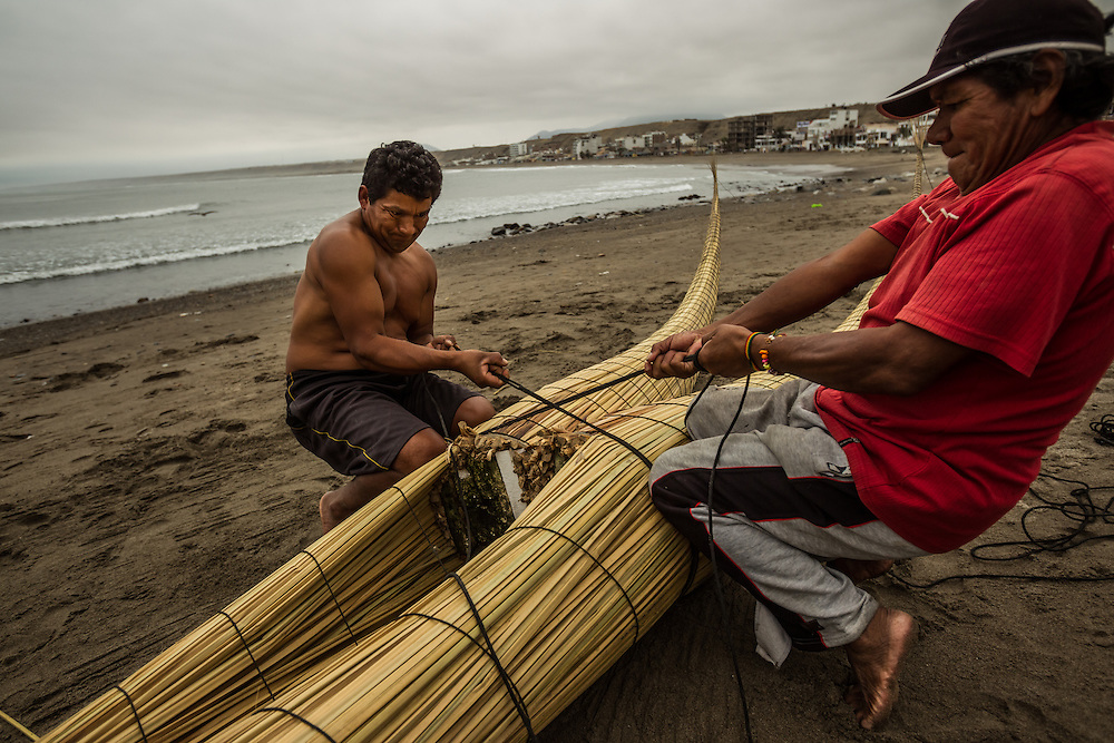 HUANCHACO, PERU - JULY 14, 2014: Carlos Ucañan Arzola, 41, (left) builds a reed boat with pointy, upswept prows known as caballitos de totora, or little totora reed horses. Centuries before the Spanish arrived and long before the Incas extended their empire from the mountaintops to the coast, fishermen here were building boats from the totora reed that grows along the shore. Today a handful of fishermen keep up that tradition, growing and harvesting the reeds and forming them into the boats that have been used by fishermen for thousands of years in Huanchaco. PHOTO: Meridith Kohut for The New York Times
