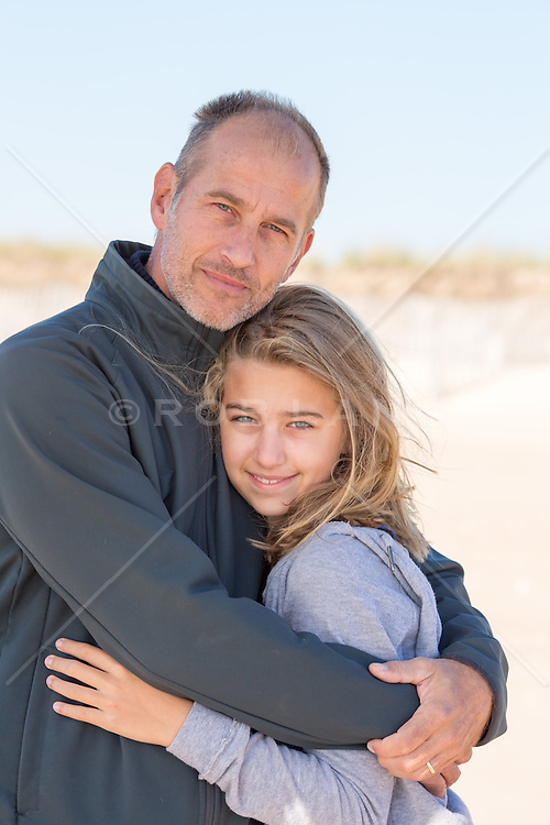 mature father and daughter embracing at the beach
