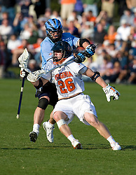 Johns Hopkins midfielder Stephen Peyser (12) collars Virginia midfielder Brian Mcdermott (26) with his stick.  The #2 ranked Virginia Cavaliers defeated the #6 ranked Johns Hopkins Blue Jays 13-12 in overtime at the University of Virginia's Klockner Stadium in Charlottesville, VA on March 22, 2008.  The loss, in front of a record UVA crowd of 7,500, was the third consecutive overtime defeat for Hopkins, the defending national champions.