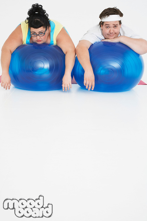 Overweight man and woman lying on Exercise Balls portrait front view
