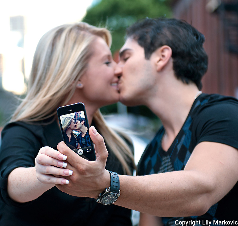 Couple kissing and taking photo with the phone