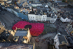"**2018 Pictures of the year by London News Pictures**<br /> © Licensed to London News Pictures 11/11/2018, Cirencester, UK. People gather to form a world record breaking (pending conformation) ""human poppy"" in Cirencester town Market Place to commemorate the end of the First World War 100 years ago today. Over 3,300 people wore coloured ponchos to create the shape of a poppy and leaf. Photo Credit : Stephen Shepherd/LNP"