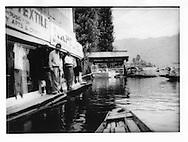 Kashmiri men wait for boats along watery main street on Dal Lake, Srinagar, Indian Administered Kashmir.