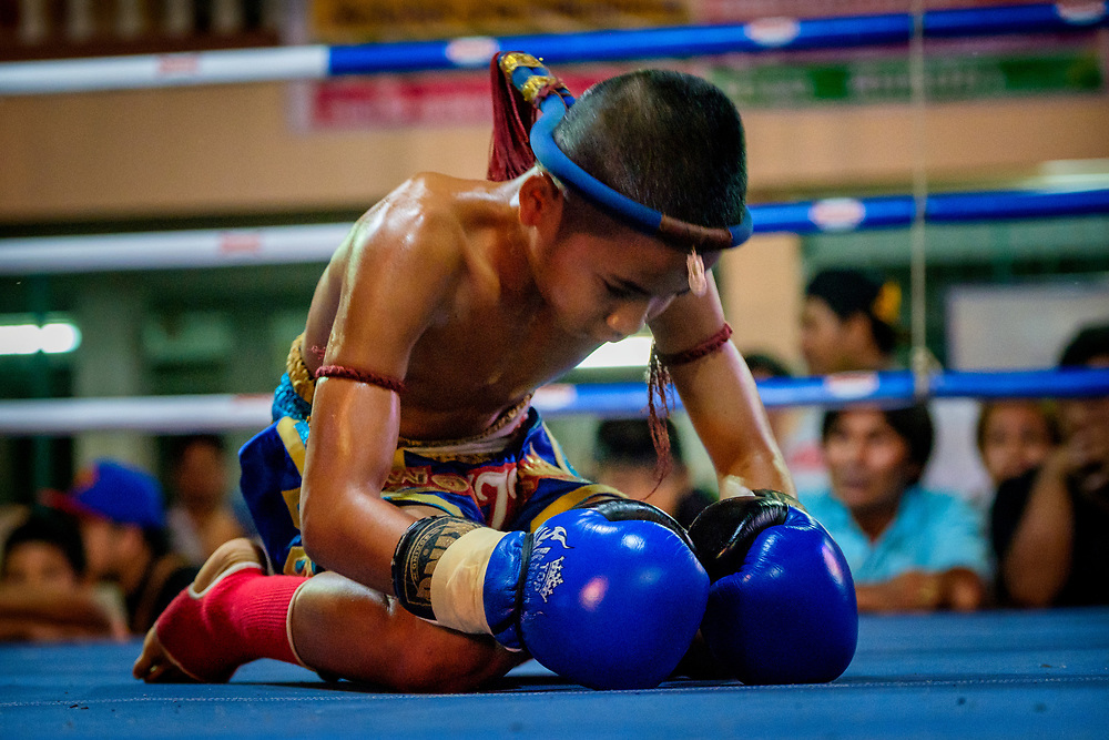 A young Muay Thai fighter performs the Wai Khru Ram Muay, a pre-fight ritual, at the beginning of a match in rural Nakhon Nayok, Thailand.