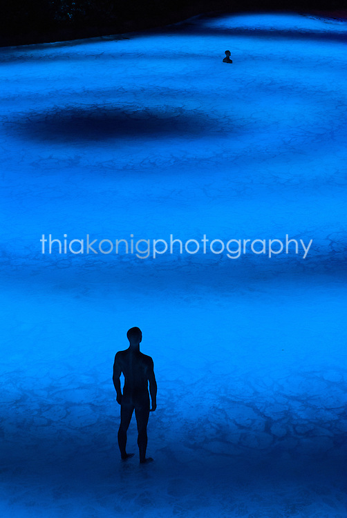 Abstract view of statue of man standing in rings of blue water. Taken from the garden terrace at the Wynn Hotel of the light and water show, Las Vegas, Nevada.