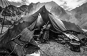 Child carries in butter tea churn into yak hair nomads tent, Khama valley, Tibet