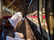 11 APRIL 2018 - BANGKOK, THAILAND:  Used bedding is thrown off the overnight Chiang Mai train at Hua Lamphong train station in Bangkok on the first day of the Songkran travel period. Songkran is the traditional Thai New Year and is one of the busiest travel periods of the year as Thais leave the capital and go back to their home provinces or resorts in tourist areas. Trains and busses are typically jammed the day before the three day Songkran holiday starts. The government has extended the official holiday period through Monday, 16 April because one day of the Songkran holiday fell on the weekend, giving many workers a five day holiday.      PHOTO BY JACK KURTZ