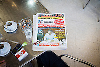 TUNIS, TUNISIA - 26 JULY 2013: A local newspaper reporting Mohamed Brahmi's death on July 25th, is here on a customer's table at the cafe of L'Etoile du Nord, where customers are unabashed about breaking the rules during Ramadan, in Tunis, Tunisia, on July 26th 2013.<br /> <br /> Tunisia, birthplace of the Arab Spring revolutionary movement, was plunged into a new political crisis on Thursday when assassins shot Mohamed Brahmi, 58, leader of the Arab nationalist People's Party, an opposition party leader outside his home in a hail of gunfire.<br /> <br /> L'Etoile du Nord, besides being a cafe, is also an experimental theater that never closes, a free-wheeling space for spectators and performers, and a haunt for actors, intellectuals, free-thinkers and revolutionaries.<br /> <br /> Tunisian actor and theater director, Noureddine El Ati, who founded the theater company in 1997, says the venue is unique in all of North Africa.