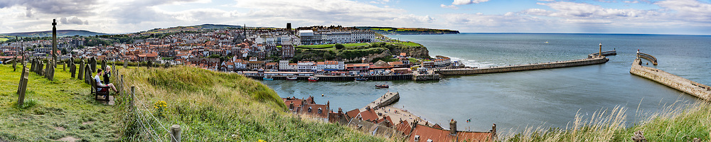 In Bram Stoker's famous 1897 novel, Dracula came ashore as a creature resembling a large dog who climbed the dramatic 199 Church Steps to the graveyard of Church of Saint Mary, shown here atop East Cliff, above Whitby at the mouth of the Esk River. The Church of Saint Mary the Virgin is an Anglican parish church serving the towns of Whitby and Ruswarp in North Yorkshire county, England, United Kingdom, Europe. Founded around 1110 AD, the church has a tower and transepts dating from the 1100s and 1200s, and interior dating mostly from the late 1700s. Seen on our England Coast to Coast hike day 13 of 14. [This image, commissioned by Wilderness Travel, is not available to any other agency providing group travel in the UK, but may otherwise be licensable from Tom Dempsey – please inquire at PhotoSeek.com.] This image was stitched from multiple overlapping photos.