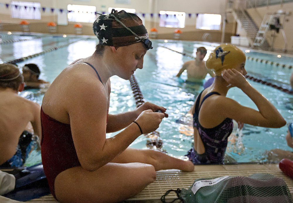 Lehi High School swimmer Amy Chapman sets her interval timer during practice at the Lehi Legacy Center, Tuesday, Dec. 18, 2012. Chapman, 17, was born with fibular hemimelia and had both legs amputated when she was 13 months old.