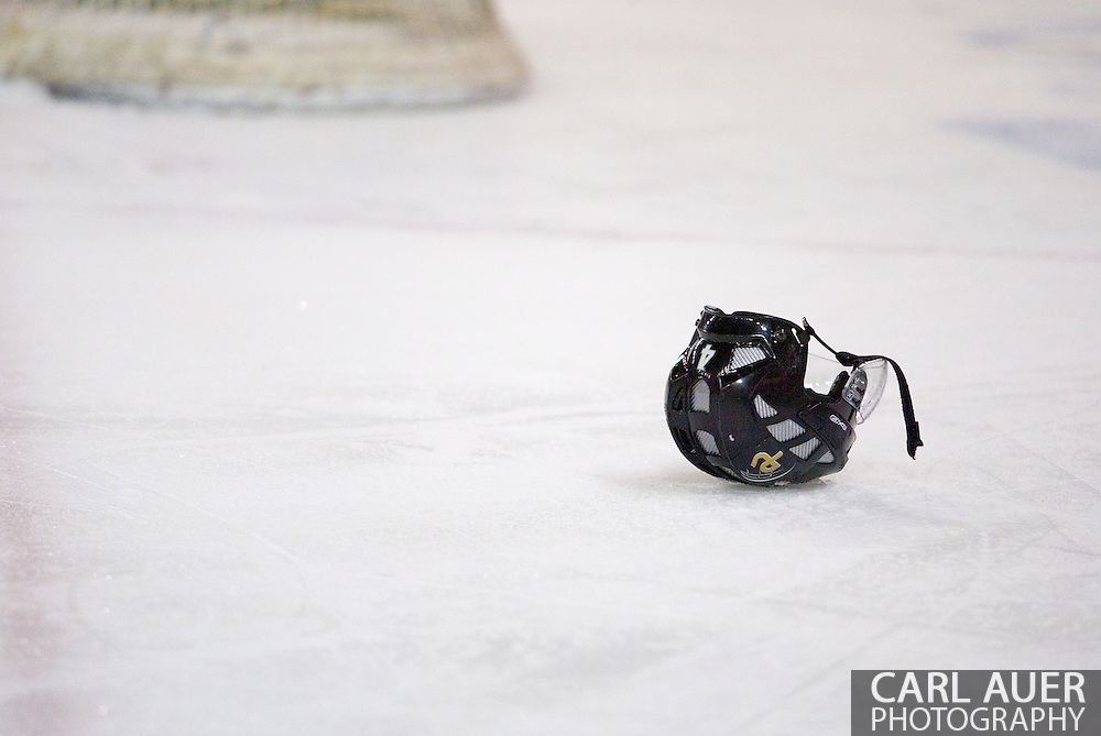 19 February, 2006 - Anchorage, AK:  Peter Metcalf's helmet sits on the ice as he pleads with the referees to explain why they did not call the hard hit that took the helmet clear off of his head.  The Alaska Aces would go on to take a overtime victory, 3-2 against the visiting Long Beach IceDogs at the Sullivan Arena.
