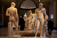 A collection of Ancient Greek statues of naked men on display at The Louvre, Paris, France.