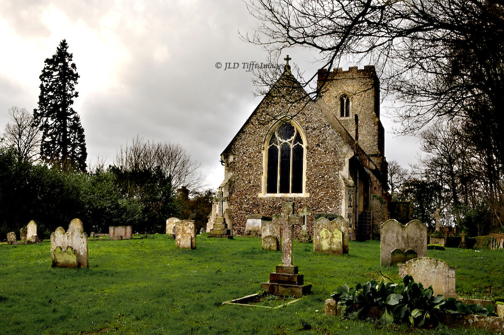 In the village of Brent Eleigh, the church of St. Mary's is a perfect example of the village church.  The chancel window is Victorian Gothic, but the church interior has been revealed to have late 14th century wall paintings of St. John, the Virgin Mary, the Harrowing of Hell, and other subjects.  For known history, see http://www.suffolkchurches.co.uk/brent.html.  This photo was made on a cloudy grey winter day, but the grass is bright green against the warm yellowish and reddish colored stone from which the church was built..