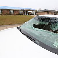 A cars windshield remains broken out along Fair Oaks Drive while several nearby home have their roofs patched as well following last weeks tornado.