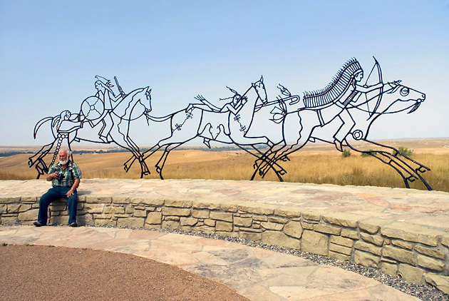 Indian Memorial to Cheyenne & Arapaho; open sculpture; grassy plains beyond; visitor; Little Bighorn Battlefield National Monument; Crow Agency; MT; Montana