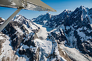 """Aerial view of Gilman Glacier in Glacier Bay National Park,  Fairweather Range, St. Elias Mountains, Alaska, USA. Flightseeing from Skagway or Haines is a spectacular way to see Glacier Bay. We were bedazzled by Mountain Flying Service's 1.3-hour West Arm tour from Skagway. Glacier Bay is honored by UNESCO as part of a huge Biosphere Reserve and World Heritage site shared between Canada and the United States. In 1750-80, Glacier Bay was totally covered by ice, which has since radically melted away. In 1794, Captain George Vancover found Icy Strait on the Gulf of Alaska choked with ice, and all but a 3-mile indentation of Glacier Bay was filled by a huge tongue of the Grand Pacific Glacier, 4000 feet deep and 20 miles wide. By 1879, naturalist John Muir reported that the ice had retreated 48 miles up the bay. In 1890, """"Glacier Bay"""" was named by Captain Beardslee of the U.S. Navy. Over the last 200 years, melting glaciers have exposed 65 miles of ocean. As of 2019, glaciers cover only 27% of the Park area. Since the mid 1900s, Alaska has warmed 3 degrees Fahrenheit and its winters have warmed nearly 6 degrees. Human-caused climate change induced by emissions of greenhouse gases continues to accelerate warming at an unprecedented rate. Climate change is having disproportionate effects in the Arctic, which is heating up twice as fast as the rest of Earth."""