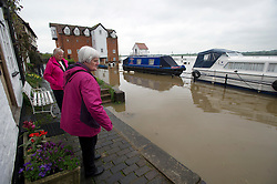 © London News Pictures. 01/05/2012. Tewkesbury, UK. Two elderly ladies look at flood water which is approaching houses in Tewkesbury, Gloucestershire, England on May 1, 2012. The UK has had its wettest April in over a century, with some areas seeing three times their usual average rainfall, according to figures from the Met Office. Photo credit : Ben Cawthra /LNP