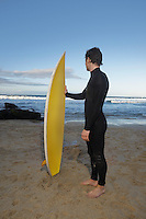 Man holding surfboard standing on beach side view