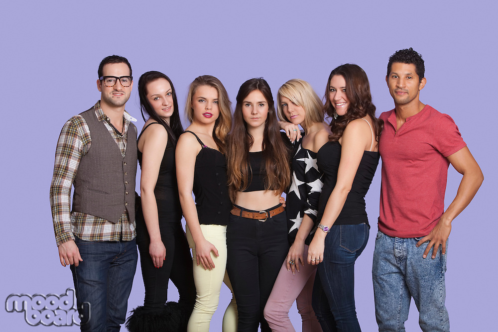 Group portrait of casual multi ethnic friends posing over purple background