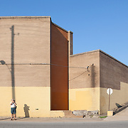 Single man photographing against a stark yellow building with light pole shadow.