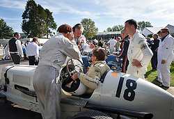 **CAPTION CORRECTION. Picture originally sent with wrong date. Picture was taken TODAY 11/09/2015** © licensed to London News Pictures. 11/09/2015<br /> Goodwood Revival Weekend, Goodwood, West Sussex. UK.<br /> The Goodwood Revival is the world's largest historic motor racing event. Competitors and enthusiasts dress in period fashions recreating the glorious days of the race circuit.<br /> Pictured. Mechanics and driver with their classic cars enter the paddock area.<br /> <br /> Photo credit : Ian Whittaker/LNP
