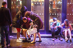 © licensed to London News Pictures. London, UK 01/01/2014. A drunk woman being helped by friends in Leicester Square, London whilst celebrating the New Year at the first hours of 2014. Photo credit: Tolga Akmen/LNP