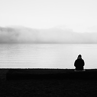 A person sitting on the beach during a sunrise, watching the fog roll in.