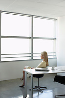 Business woman looking through window sitting in office