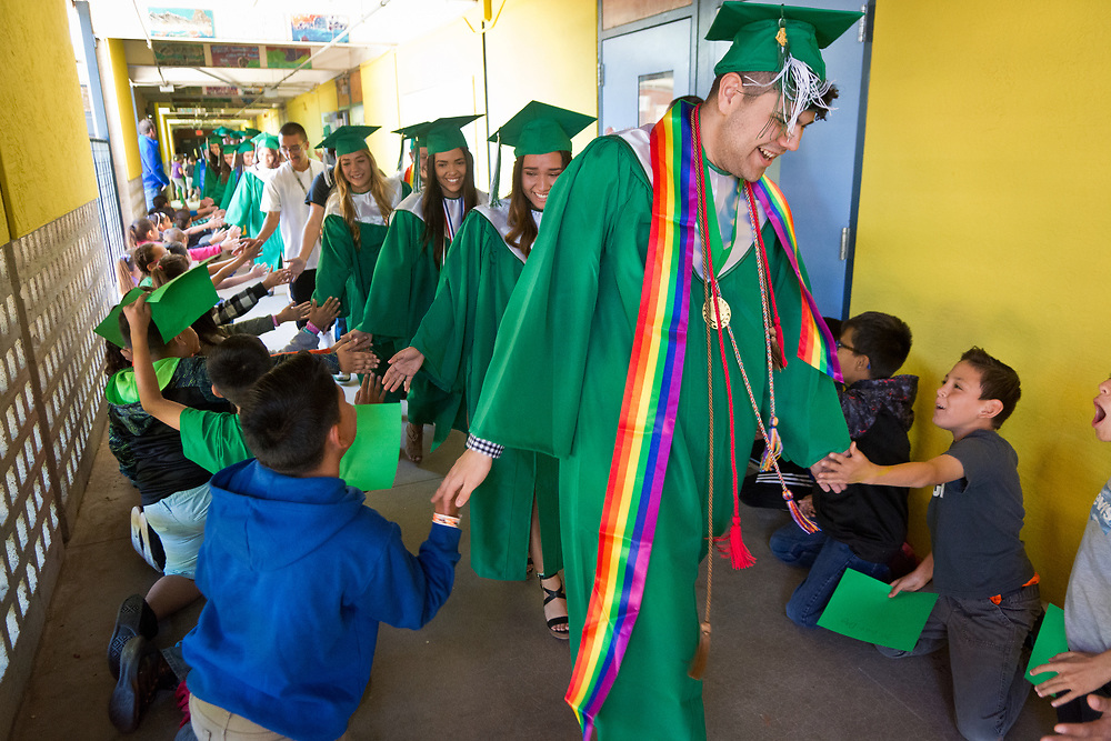 "mkb051217a/metro/Marla Brose -- Albuquerque High graduating senior Aidan Martinez, front, high fives a class of students, including Craig Janis, bottom right, who line the halls of  East San Jose Elementary, Friday, May 12, 2017, in Albuquerque, N.M. The school's students cheered on a group of graduates as they walked around the school which was decorated with congratulations. The graduates are visiting other schools in their cluster to visit with young students and offer them a view of graduation. Albuquerque High School graduation ceremony will be Monday, May 15. ""I felt like a rock star,"" said Tuesday Chavez, one of the Albuquerque High graduates. (Marla Brose/Albuquerque Journal)"