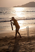 Man playing cricket on the beach at sunset in Goa (India)