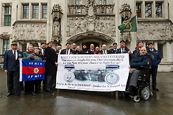 © Licensed to London News Pictures. 14/03/2019. London, UK.  Members of the Justice for NI Veterans pose for photograph as they wait for veteran Dennis Hutchings to arrive at the Supreme Court in London for the latest hearing in his challenge against the decision to hold his trial over an incident in Northern Ireland during the troubles without a jury.  Photo credit: Vickie Flores/LNP