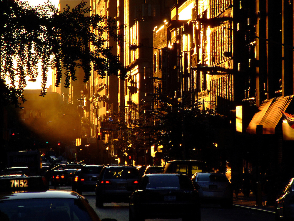 Sunset on 29th street with buildings, taxi, and traffic<br />